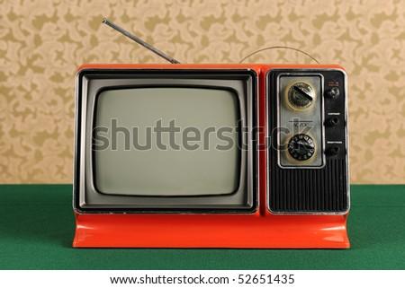 Orange vintage television in 1970s environment - stock photo