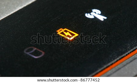Orange warning low battery signal on a laptop along with turned on wifi - stock photo