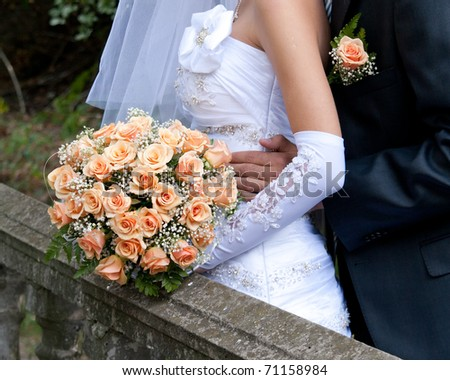orange wedding bouquet in the hands of the bride, next to the groom in a park - stock photo