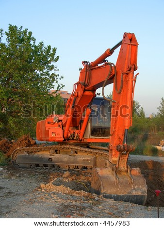 Orange wheeled excavator in a construction site - stock photo