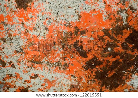 Orange White Gray and Rust Colored Background on Side of Old Wheel Barrow - stock photo