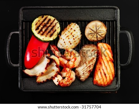 orange white red and green hot barbecue vegetables and seafood - stock photo