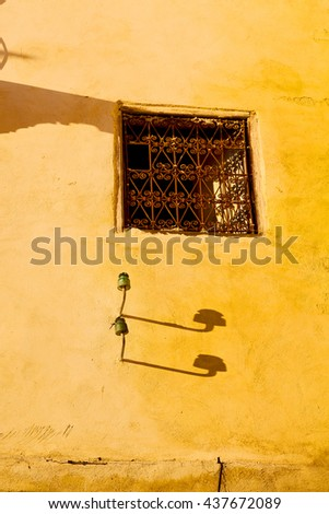 orange   window in morocco africa old construction and brown wall red carpet