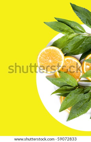 Orange with leaves on the yellow background - stock photo