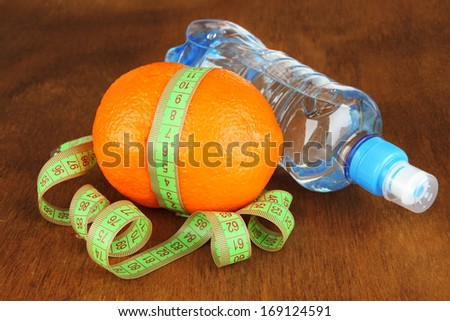 Orange with measuring tape, bottle of water, on wooden background - stock photo
