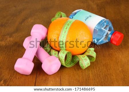 Orange with measuring tape,dumbbells and bottle of water, on wooden background - stock photo