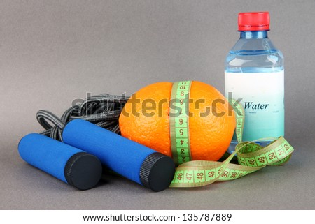 Orange with measuring tape,skipping rope and bottle of water, on color background - stock photo