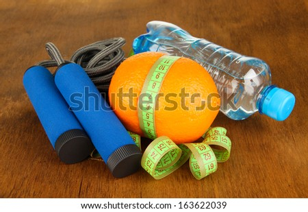 Orange with measuring tape,skipping rope and bottle of water, on wooden background - stock photo