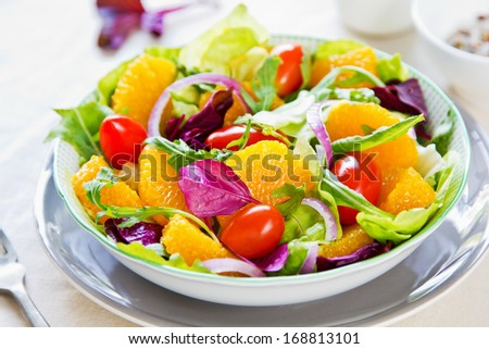 Orange with rocket and lettuce salad in a bowl - stock photo
