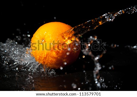 orange with splashes of water on a black background