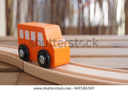 Orange wooden toy bus on a track on wooden table