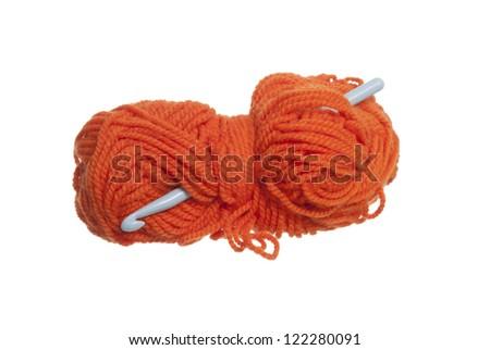 Orange wool and crochet hook on white background. - stock photo