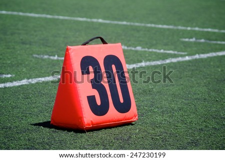 Orange yard marker designates the thirty yard line on a football field. - stock photo