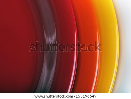 orange, yellow and red colored  plates stacked upon each other. This set of kitchen ware is made of melamine plastic - stock photo