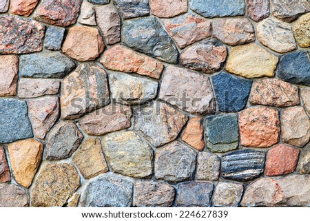 Orange, yellow, red, blue, purple stones and pebbles on  gray wall, background, closeup - stock photo