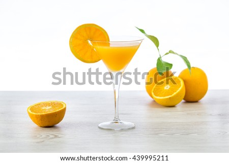 oranges and glass of juice on a wooden table and white background - stock photo