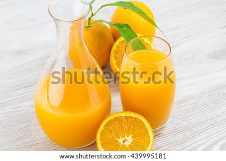 oranges and glass of juice on a wooden table. Closeup - stock photo
