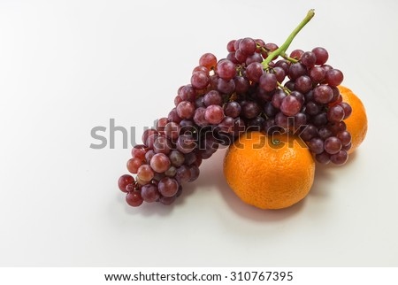 Oranges and grapes on white background - stock photo
