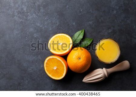 Oranges and juice glass on stone background. Top view with copy space