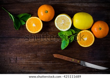 Oranges and lemons with leaves on wooden background. - stock photo