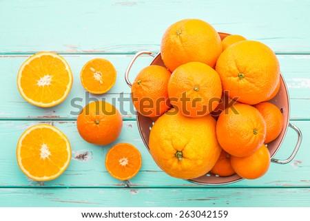 Oranges and Tangerines in retro colander. - stock photo