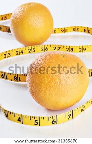 Oranges and tape measure on a reflective tabletop