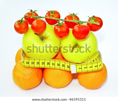 Oranges, apples and tomatoes with measuring tape