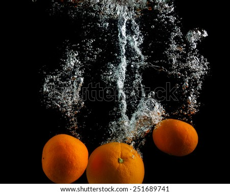 Oranges fall in the water with air bubbles. Photo on black background. - stock photo