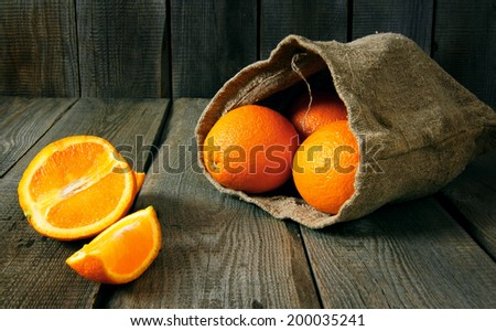 Oranges in an old bag. On a wooden background. - stock photo
