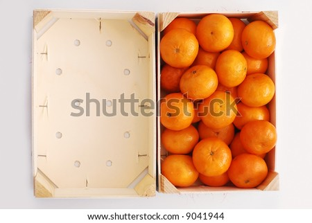 Oranges in the wooden crate near an empty crate