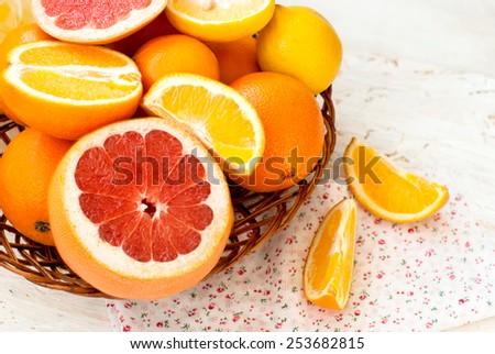 oranges, lemons, grapefruit vase whole and sliced - stock photo