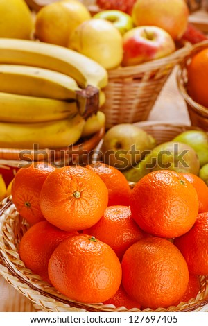 Oranges, pears, bananas and apples in wicker basket. - stock photo