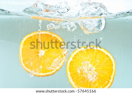 Oranges splashing into water - stock photo