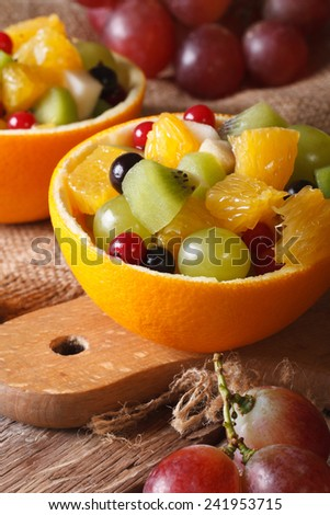 Oranges stuffed with fresh fruit salad close-up on the table. Vertical  - stock photo