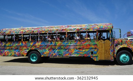 ORANJESTAD, ARUBA - NOV 26: Colorful tour bus in Aruba, as seen on Nov 26, 2015. About three quarters of the Aruban gross national product is earned through tourism or related activities. - stock photo