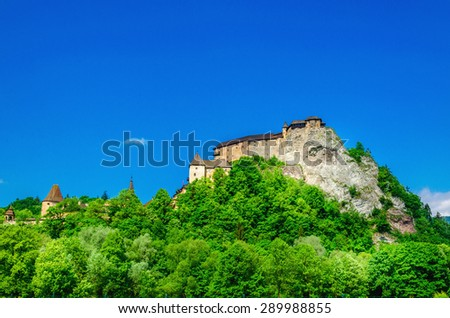 Orava Castle on a background of green trees and blue sky, one of the most beautiful Slovak castles, Orava Podzamcze, Slovakia - stock photo