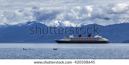 Orca whales and cruise liner are shown on snow mountains background, Alaska, the USA - stock photo