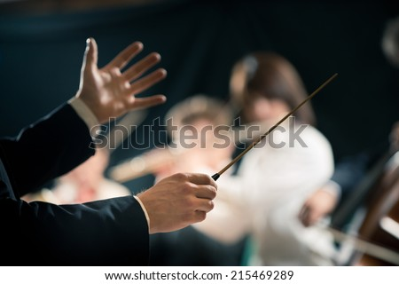 Orchestra conductor directing symphony orchestra with performers on background, hands close-up. - stock photo