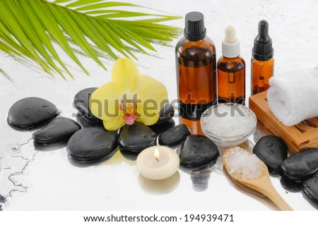 Orchid and burn candles ,black stones, oil , palm, towel on wet background - stock photo