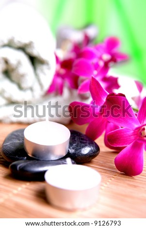 Orchid and candles with towels and pebbles. Time to relax, indulge and unwind.