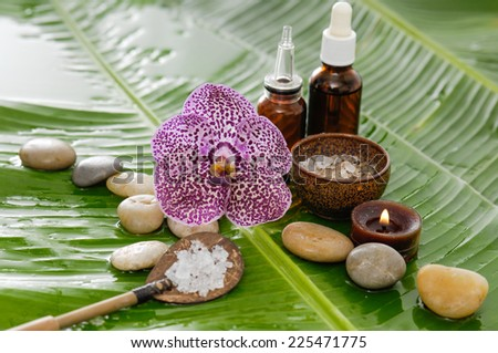 orchid and stones ,oil with burning candle on wet banana leaf