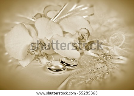Orchid bouquet with wedding rings on pillow in sepia tone - stock photo