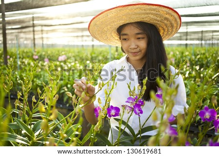 orchid farm, Young Asian girl wearing weave hat in orchid farm - stock photo
