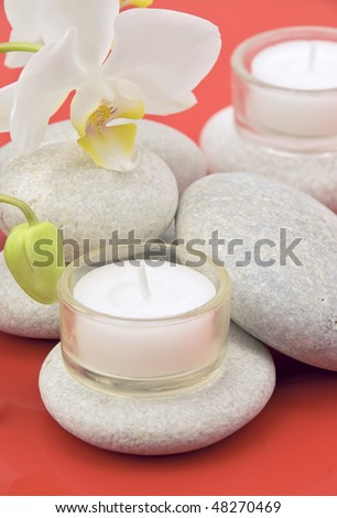 Orchid flower, natural sea stones and candles. Close up, shallow dept of field