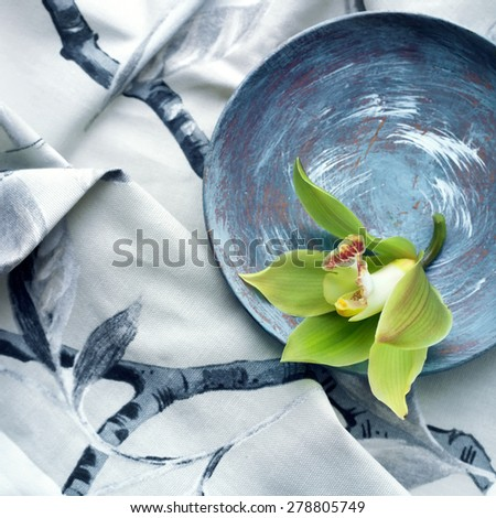 Orchid flower set against a grey printed fabric, age defying beauty concept - stock photo