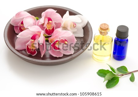 Orchid flowers on the plate and essential oil with mint leaf