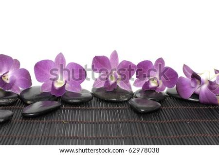 Orchid on massage stones on bamboo stick straw mat - stock photo