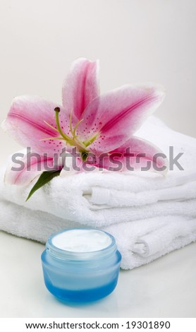 Orchid, towel and moisturizer isolated on glass