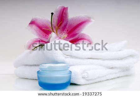 Orchid, towel and moisturizer isolated on glass - stock photo