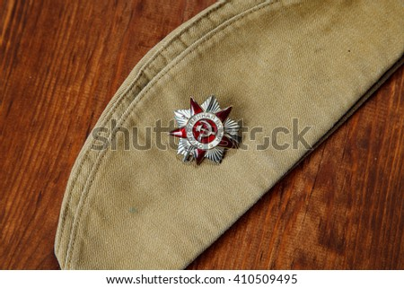 Order of the Patriotic War in St. on a Soldier's forage cap on a wooden. background - stock photo